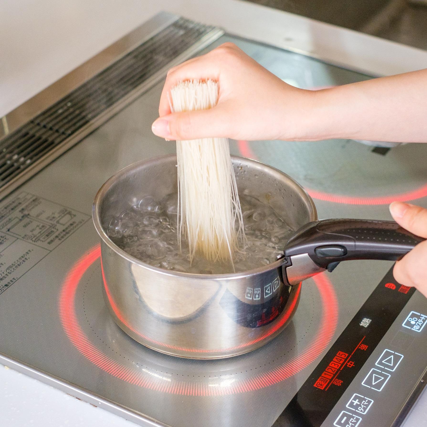 ビーフンをお湯がフツフツとなる火加減で4分間ゆがき、4分後ザルにとり、流水でよく冷やしてしっかり水気を切る。